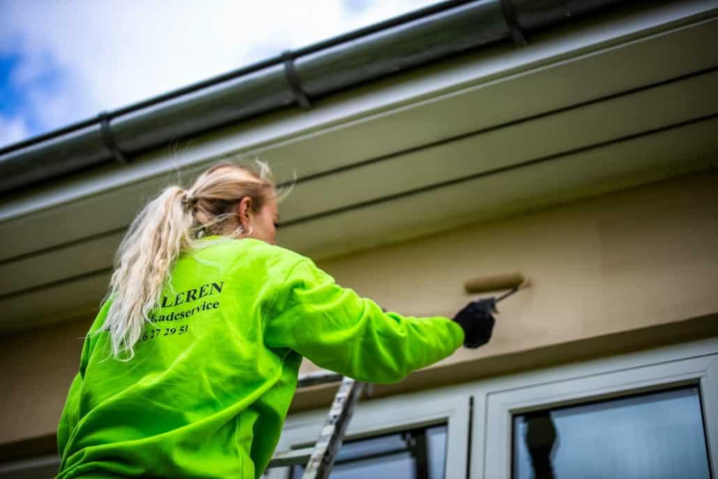 Maler i gang med at male en facade